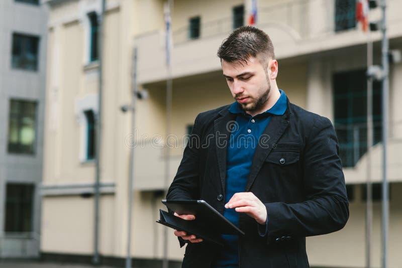 Υπαίθριο πορτρέτο του σύγχρονου επιχειρηματία σε ένα κοστούμι που λειτουργεί σε μια ταμπλέτα στο υπόβαθρο του εμπορικού κέντρου στοκ φωτογραφία με δικαίωμα ελεύθερης χρήσης