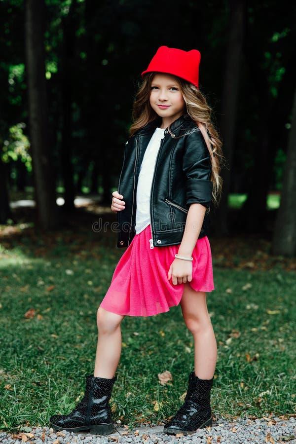 Υπαίθριο πορτρέτο τρόπου ζωής του μοντέρνου εφήβου μικρών κοριτσιών στο πάρκο πόλεων Όμορφο παιδί, φθορά στοκ εικόνες
