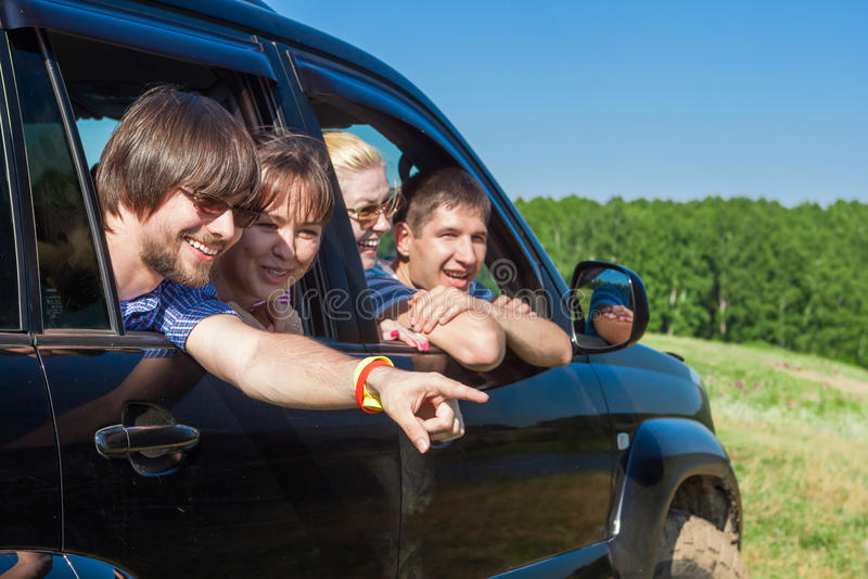 Υπαίθριο πορτρέτο των νέων που φαίνονται έξω το μαύρο αυτοκίνητο παραθύρων στοκ φωτογραφία