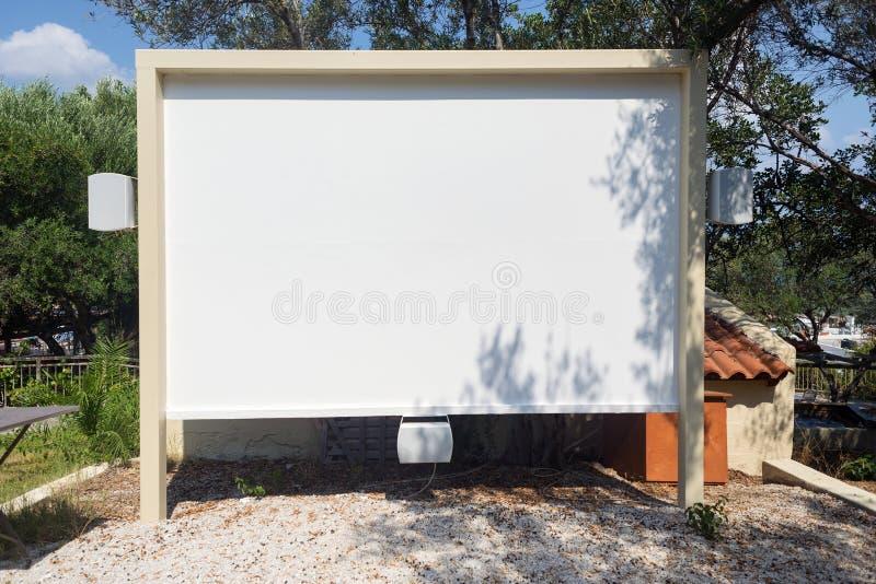 Υπαίθριο προβολέων ξενοδοχείο σεμιναρίου κινηματογράφων οθόνης σπιτικό με το κενό καθισμάτων στοκ φωτογραφία με δικαίωμα ελεύθερης χρήσης
