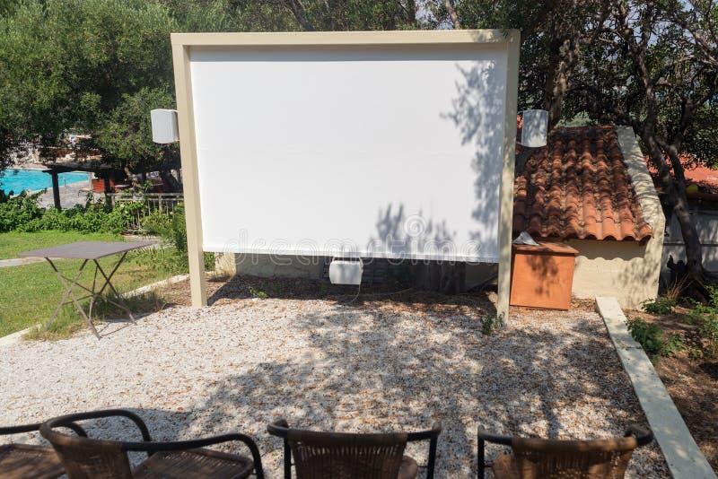 Υπαίθριο προβολέων ξενοδοχείο σεμιναρίου κινηματογράφων οθόνης σπιτικό με το κενό καθισμάτων στοκ φωτογραφίες