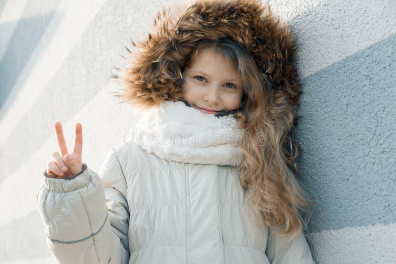 Υπαίθριο χειμερινό πορτρέτο κινηματογραφήσεων σε πρώτο πλάνο του παιδιού, ξανθό κορίτσι με τη σγουρή τρίχα 7, 8 έτη στην κουκούλα στοκ εικόνες