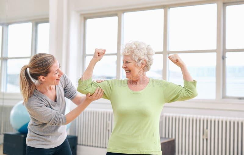 Υπερήφανη ηλικιωμένη γυναίκα που λυγίζει το bicep της με τον προσωπικό εκπαιδευτή στοκ εικόνα με δικαίωμα ελεύθερης χρήσης