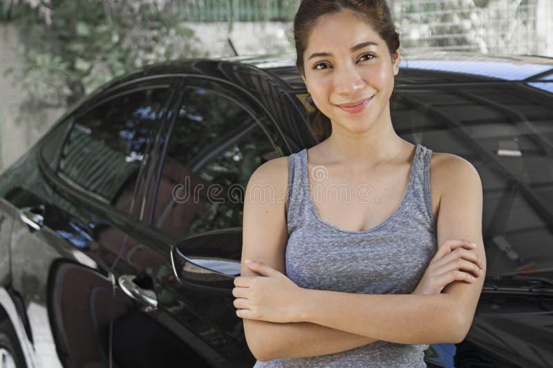 Υπερήφανη νέα κυρία με ένα αυτοκίνητο στοκ φωτογραφία με δικαίωμα ελεύθερης χρήσης