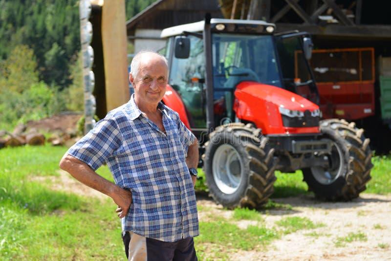 Υπερήφανος αγρότης που στέκεται μπροστά από το τρακτέρ του στοκ εικόνα