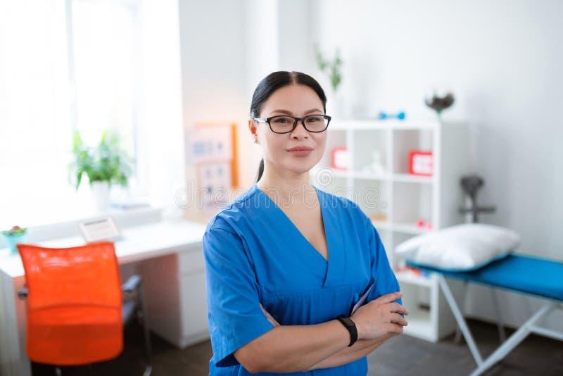 Υπερήφανος ασιατικός σκοτεινός-μαλλιαρός φυσιοθεραπευτής που φορά επαγγελματικό μπλε ομοιόμορφο στοκ εικόνες