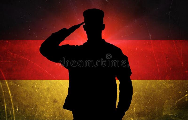 Υπερήφανος γερμανικός στρατιώτης στο γερμανικό υπόβαθρο σημαιών ελεύθερη απεικόνιση δικαιώματος