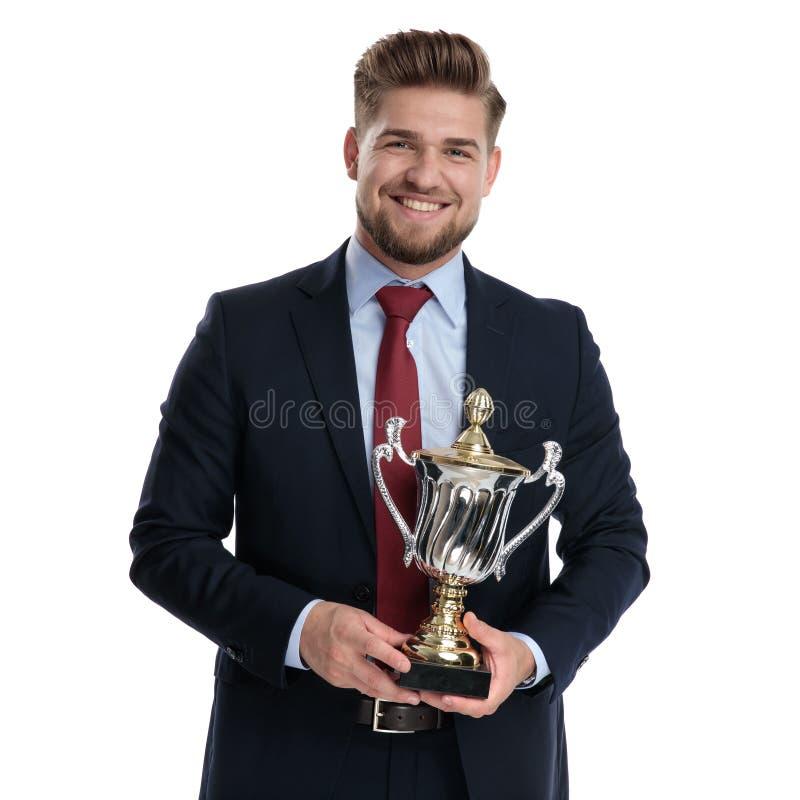 Υπερήφανος επιχειρηματίας που κρατά το τρόπαιο και το χαμόγελό του στοκ φωτογραφία με δικαίωμα ελεύθερης χρήσης