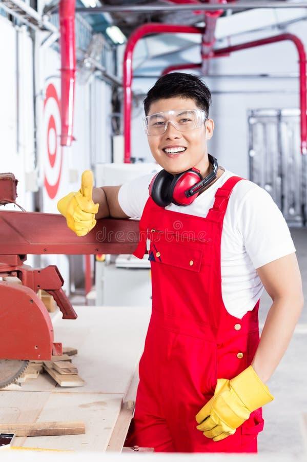 Υπερήφανος εργαζόμενος στον εργασιακό χώρο του στις βιομηχανικές εγκαταστάσεις στοκ φωτογραφία