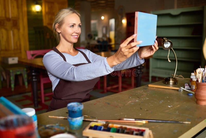 Υπερήφανος καλλιτέχνης που εξετάζει τη νέα ζωγραφική στοκ φωτογραφία