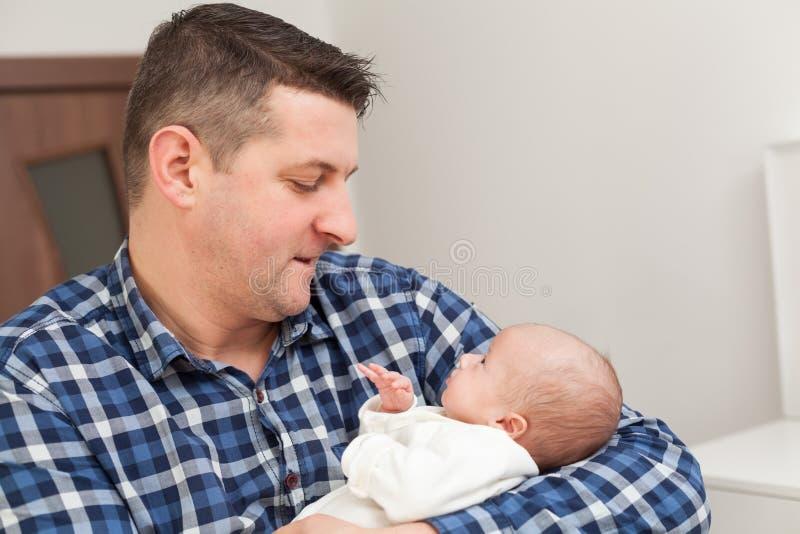 Υπερήφανος πατέρας που κρατά το νεογέννητο μωρό του στα χέρια στοκ φωτογραφίες