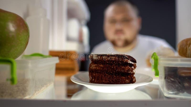 Υπεργέθες άτομο που παίρνει το κομμάτι του κέικ από το ψυγείο τη νύχτα, κίνδυνος διαβήτη, θερμίδες στοκ φωτογραφία με δικαίωμα ελεύθερης χρήσης