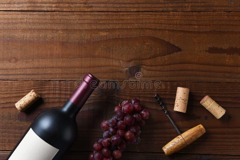 Υπερυψωμένη άποψη ενός Cabernet - sauvignon το μπουκάλι κρασιού σε μια σκοτεινή ξύλινη επιφάνεια με τα σταφύλια και τη βίδα φελλο στοκ εικόνες