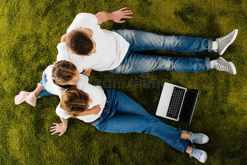 υπερυψωμένη άποψη της οικογένειας με τη στήριξη lap-top στοκ φωτογραφία