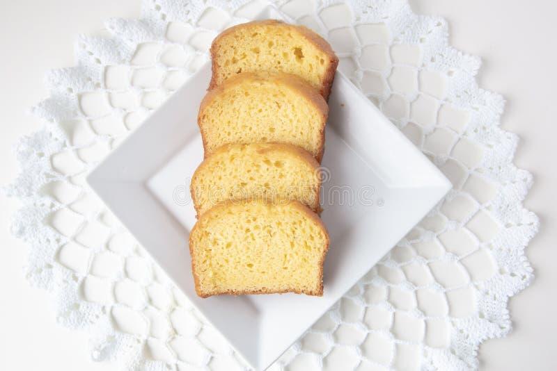 Υπερυψωμένη άποψη της φραντζόλας λεμονιών που τεμαχίζεται στο άσπρο πιάτο στοκ εικόνα