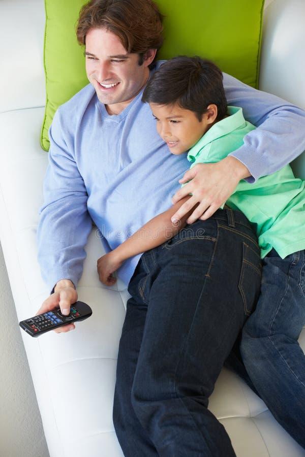 Υπερυψωμένη άποψη της χαλάρωσης πατέρων και γιων στον καναπέ που προσέχει τη TV στοκ εικόνα