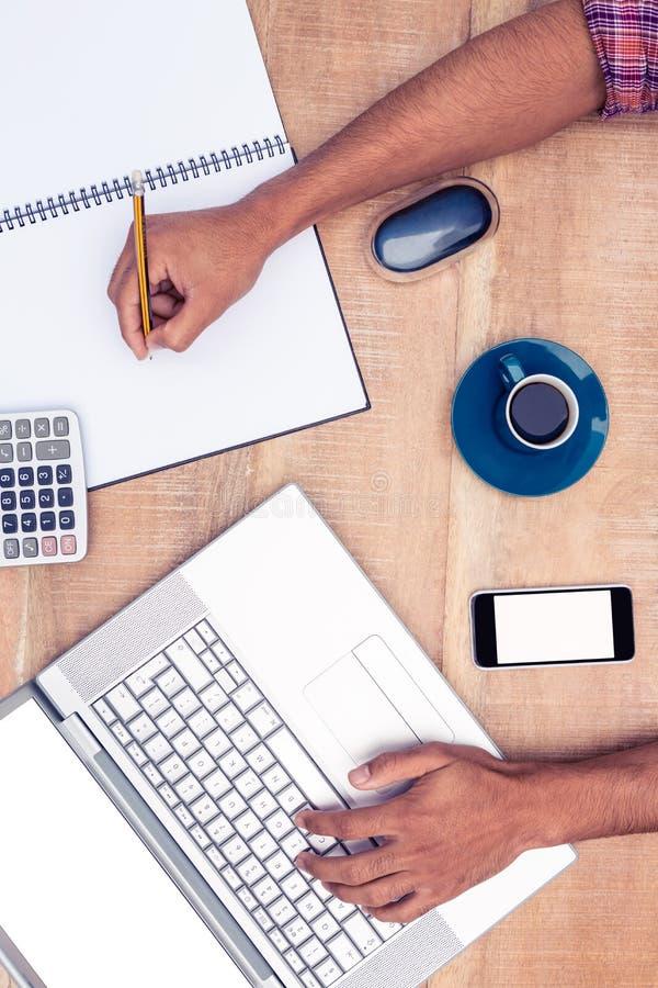 Υπερυψωμένη άποψη του γραψίματος επιχειρηματιών στο βιβλίο εργαζόμενων στο lap-top στοκ φωτογραφίες με δικαίωμα ελεύθερης χρήσης