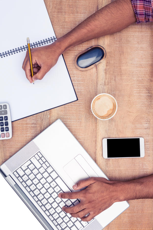Υπερυψωμένη άποψη του επιχειρηματία που εργάζεται στο lap-top γράφοντας στο βιβλίο στοκ εικόνες