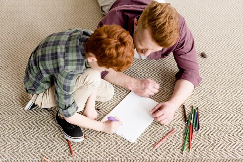 υπερυψωμένη άποψη του redhead πατέρα και του γιου που σύρουν από κοινού στοκ φωτογραφίες με δικαίωμα ελεύθερης χρήσης