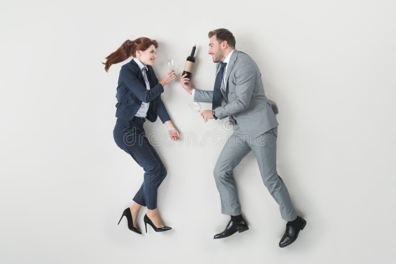 υπερυψωμένη άποψη των χαμογελώντας επιχειρησιακών συναδέλφων με το μπουκάλι του κρασιού και των γυαλιών κρασιού στοκ εικόνα με δικαίωμα ελεύθερης χρήσης