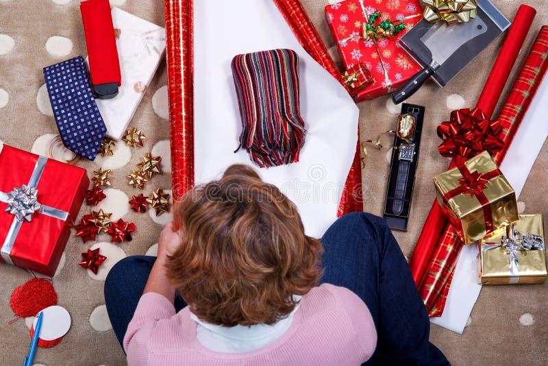 Υπερυψωμένη γυναίκα που τυλίγει τα χριστουγεννιάτικα δώρα της. στοκ φωτογραφία