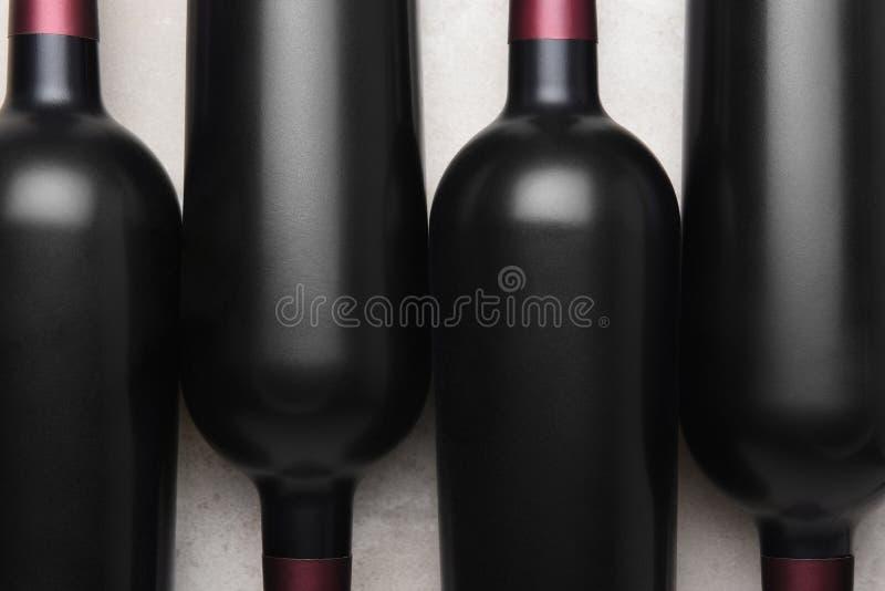 Υπερυψωμένος πυροβολισμός κινηματογραφήσεων σε πρώτο πλάνο τεσσάρων μπουκαλιών κόκκινου κρασιού στοκ εικόνα