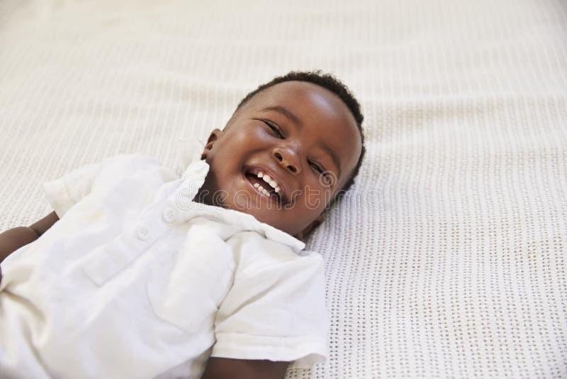 Υπερυψωμένος πυροβολισμός να βρεθεί αγοριών χαμόγελου νέο στο κρεβάτι στοκ εικόνες