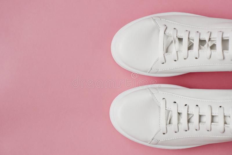 Υπερυψωμένος πυροβολισμός των άσπρων πάνινων παπουτσιών στο ρόδινο υπόβαθρο στοκ εικόνα