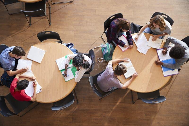 Υπερυψωμένος πυροβολισμός των μαθητών γυμνασίου στη μελέτη ομάδας γύρω από τους πίνακες στοκ εικόνα με δικαίωμα ελεύθερης χρήσης