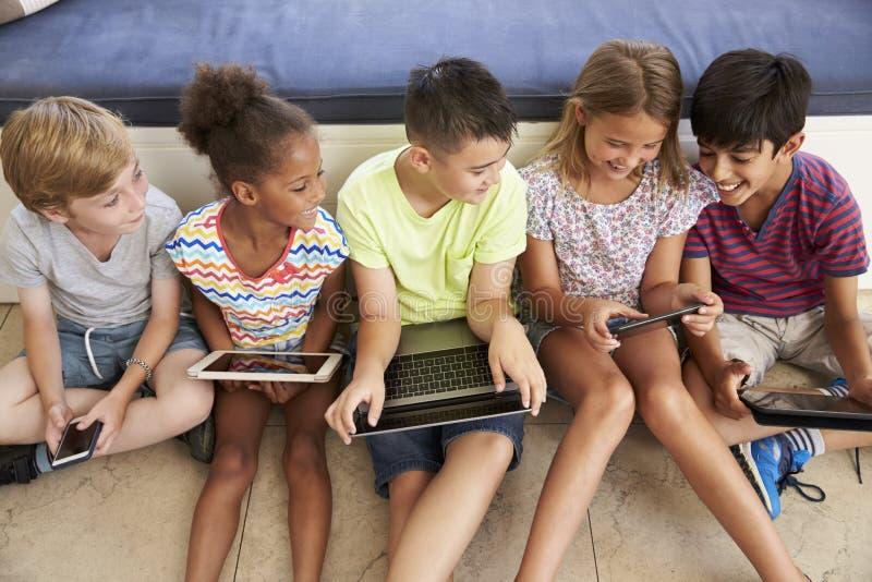 Υπερυψωμένος πυροβολισμός των παιδιών που κάθονται στο πάτωμα που χρησιμοποιεί την τεχνολογία στοκ φωτογραφία με δικαίωμα ελεύθερης χρήσης