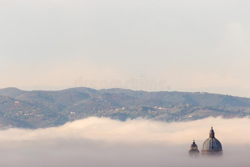 Υπερφυσική άποψη της παπικής εκκλησίας Assisi Angeli degli της Σάντα Μαρία που κρύβεται σχεδόν τελείως από την ομίχλη στοκ εικόνα