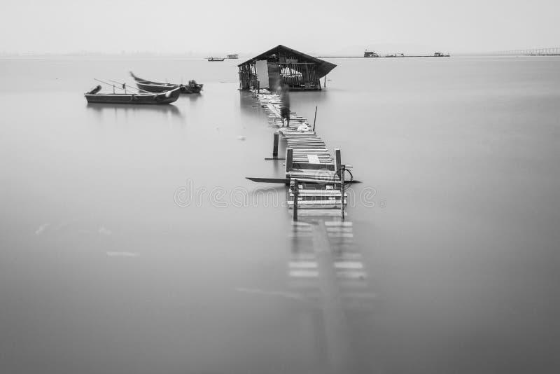 Υπερχείλιση νερού σε μια σπασμένη ξύλινη γέφυρα σε γραπτό στοκ φωτογραφία