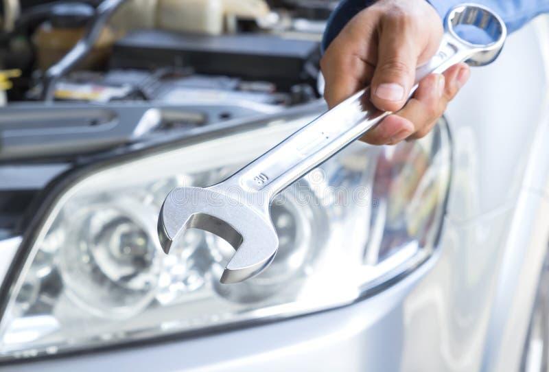 Υπηρεσία επισκευής αυτοκινήτων, αυτόματος μηχανικός που κρατά ένα γαλλικό κλειδί στοκ εικόνα