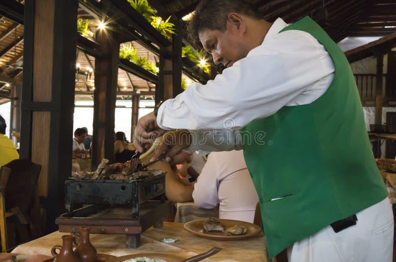 Υπηρεσία σε ένα εστιατόριο Σερβιτόρος που το ψημένο στη σχάρα κρέας στοκ εικόνα