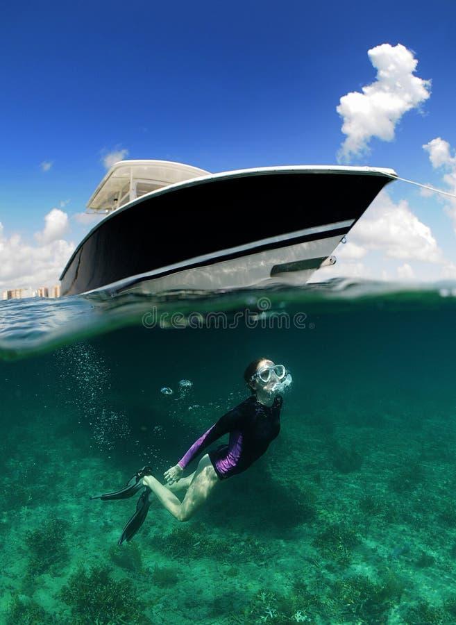 Υποβρύχια εικόνα της κολύμβησης με αναπνευστήρα γυναικών κοντά στη βάρκα στοκ εικόνες