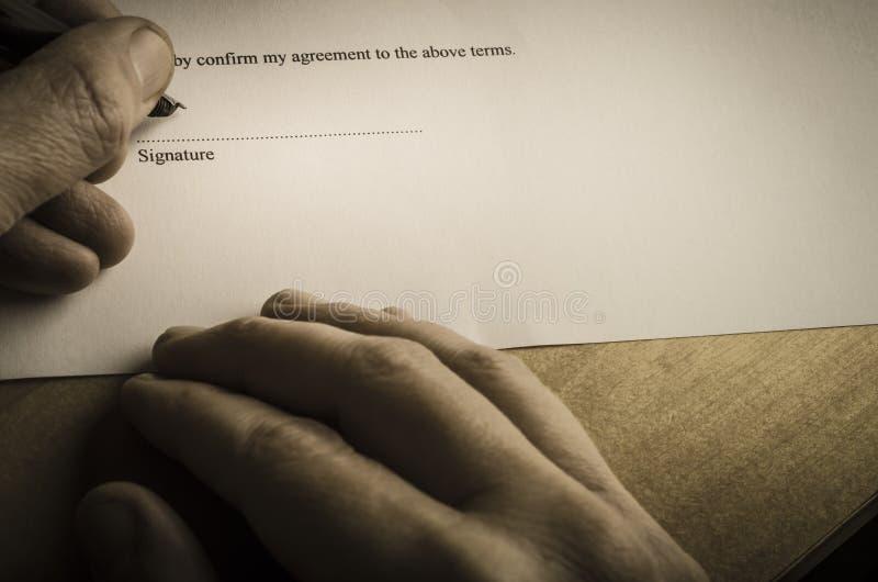 Υπογράφοντας το έγγραφο - αυστηρό φως στοκ εικόνες