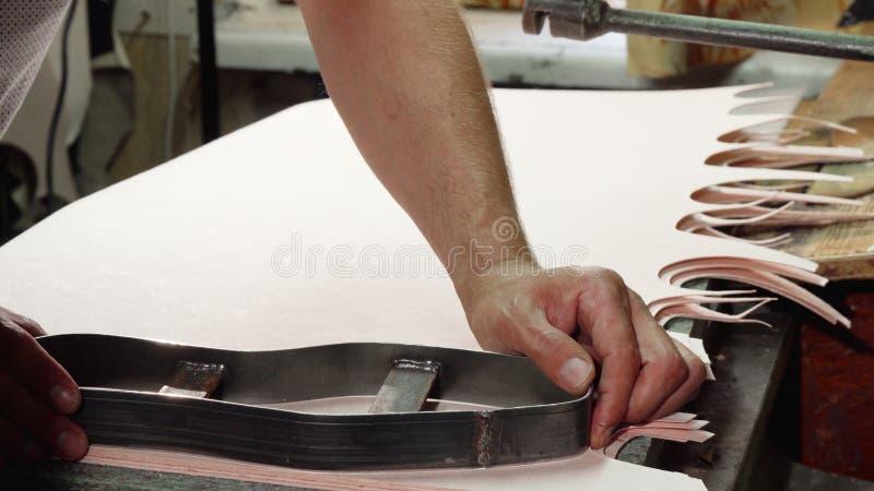Υποδηματοποιός που χρησιμοποιεί την τέμνουσα μηχανή μετζεσολών στο εργαστήριό του στοκ φωτογραφία με δικαίωμα ελεύθερης χρήσης