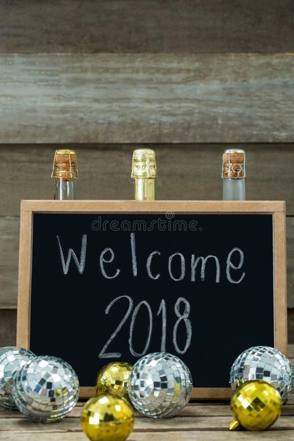 Υποδοχή 2018 που γράφεται στον πίνακα πλακών με τα μπιχλιμπίδια και το μπουκάλι σαμπάνιας στοκ φωτογραφία