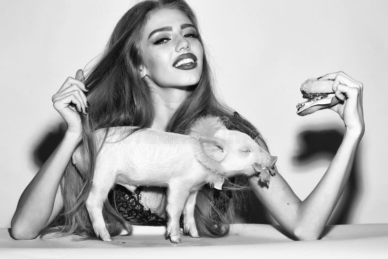 Υποκρισία και pretense Γυναίκα με burger και το pigglet στοκ φωτογραφία