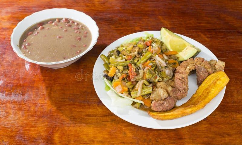 Υπολείμματα ζωϊκού λίπους χοιρινού κρέατος με τη φυτική σαλάτα, τηγανισμένα plantain και τα φασόλια - χαρακτηριστικό κολομβιανό π στοκ φωτογραφία με δικαίωμα ελεύθερης χρήσης