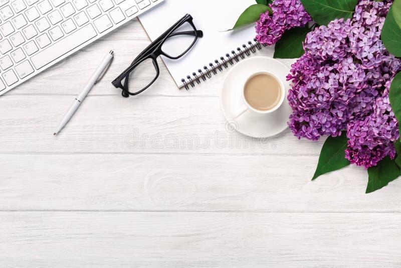 Υπολογιστής γραφείου γραφείων με μια ανθοδέσμη των πασχαλιών, του φλυτζανιού καφέ, του πληκτρολογίου, του σημειωματάριου και της  στοκ φωτογραφίες