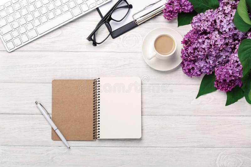 Υπολογιστής γραφείου γραφείων με μια ανθοδέσμη των πασχαλιών, του φλυτζανιού καφέ, του πληκτρολογίου, του σημειωματάριου και της  στοκ φωτογραφία
