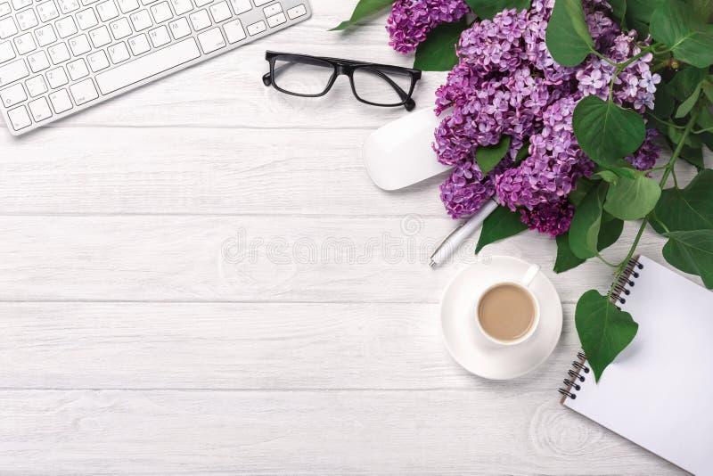 Υπολογιστής γραφείου γραφείων με μια ανθοδέσμη των πασχαλιών, του φλυτζανιού καφέ, του πληκτρολογίου, του σημειωματάριου και της  στοκ εικόνα