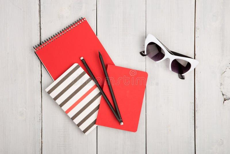 υπολογιστής γραφείου με τα σημειωματάρια κοκκίνου και λουρίδων, pensils, γυαλιά ηλίου σε ένα wh στοκ εικόνες με δικαίωμα ελεύθερης χρήσης