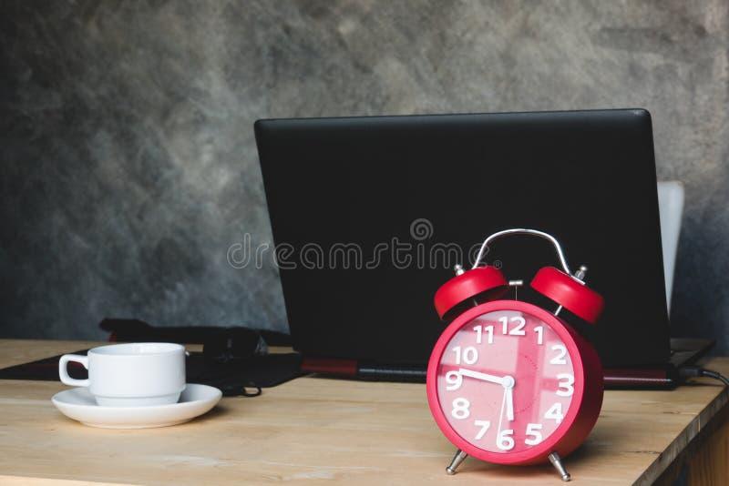 Υπολογιστής γραφείου με το κόκκινο ξυπνητήρι και φλιτζάνι του καφέ με το σημειωματάριο ομο στοκ φωτογραφία με δικαίωμα ελεύθερης χρήσης
