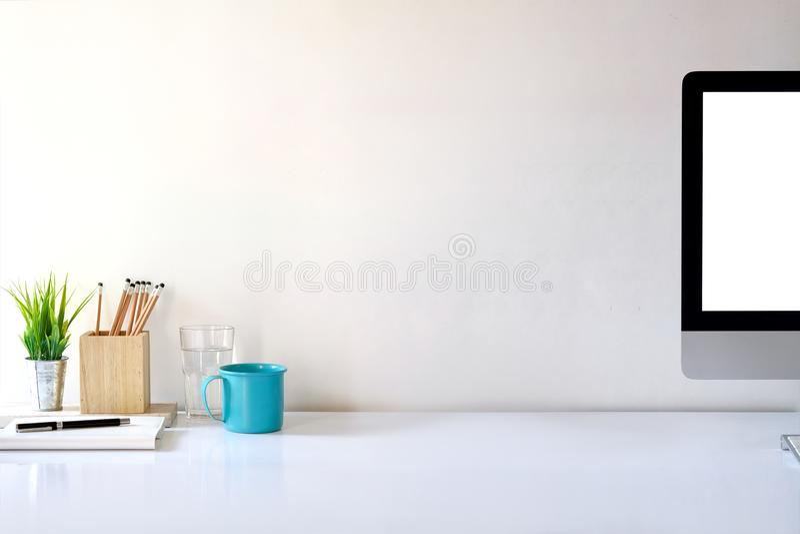 Υπολογιστής γραφείου προτύπων που παρουσιάζει άσπρο διάστημα οθόνης και αντιγράφων στον πίνακα γραφείων στούντιο στοκ εικόνες