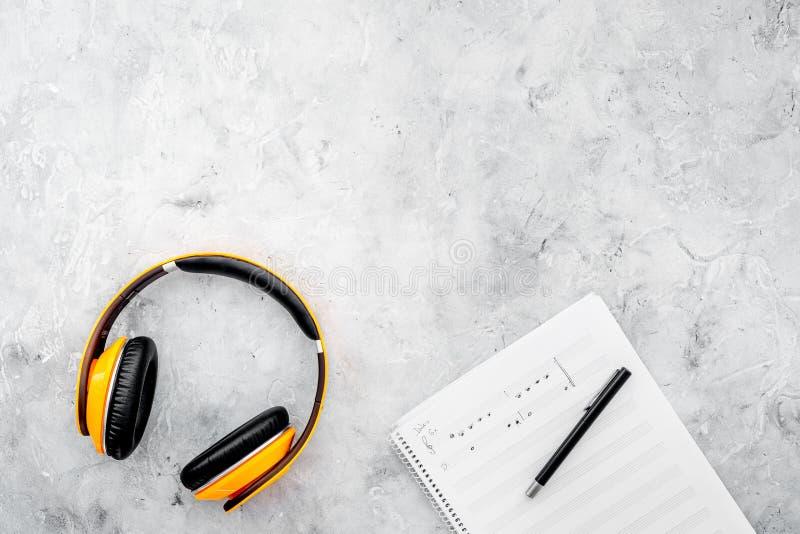 Υπολογιστής γραφείου συνθετών και συγγραφέων τραγουδιού με τα ακουστικά και τις σημειώσεις για τη τοπ χλεύη άποψης υποβάθρου πετρ στοκ εικόνες