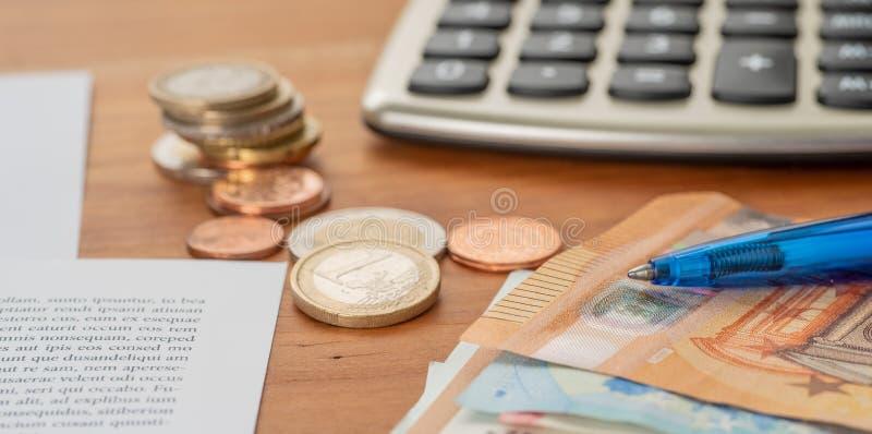 Υπολογιστής με τους ευρο- λογαριασμούς και τους σωρούς νομισμάτων στοκ φωτογραφίες