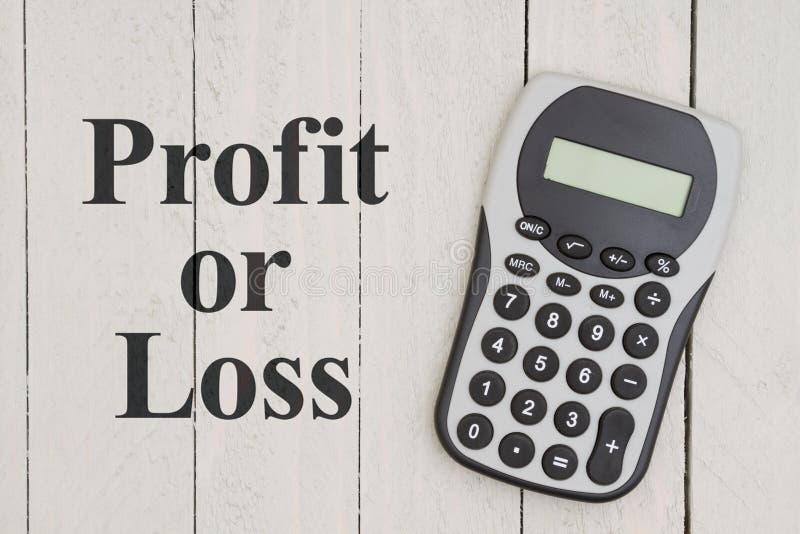 Υπολογιστής στο ξεπερασμένο ξύλο με το κέρδος ή την απώλεια κειμένων στοκ εικόνα