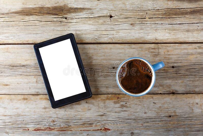Υπολογιστής ταμπλετών και ένα φλυτζάνι του μαύρου καφέ σε έναν ξύλινο πίνακα επάνω από την όψη στοκ φωτογραφίες με δικαίωμα ελεύθερης χρήσης